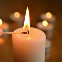 Lighting pillar candle with tealights in background