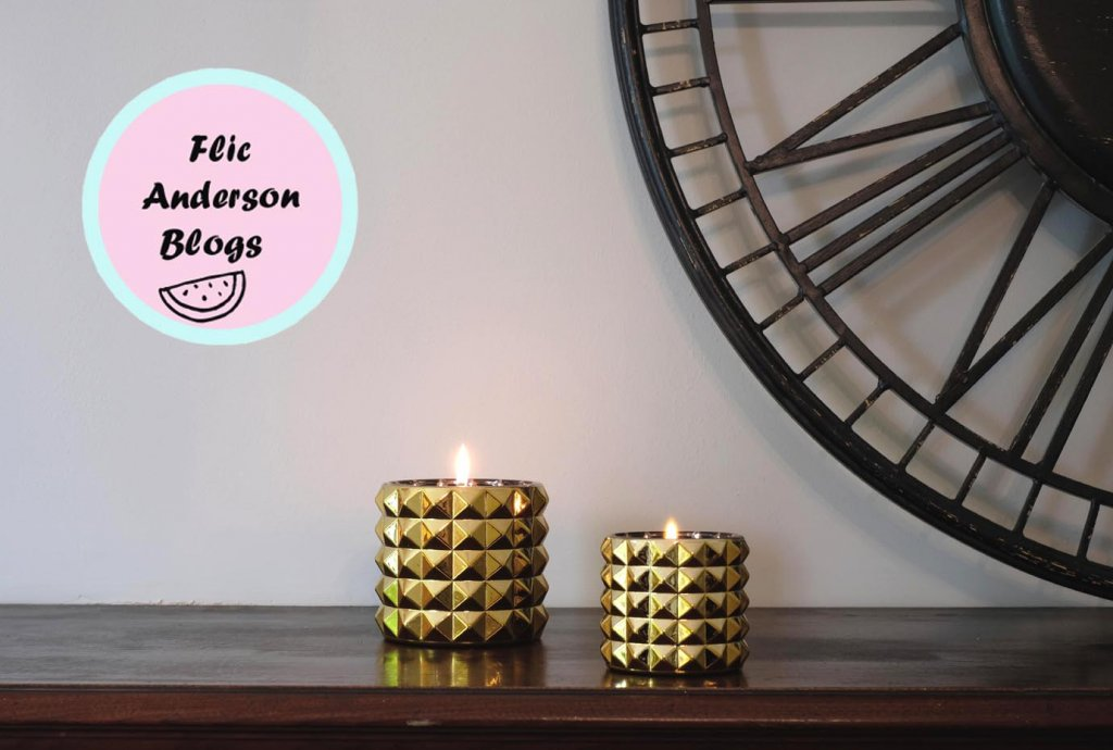 Gold candles on table with black decorative clock