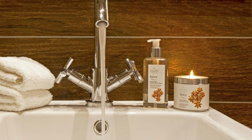 candle and handwash at sink with towel